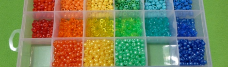 "Image Description: a Jarvis Walker worm-proof lure-box with adjustable compartments. There's four compartments down and six compartments across. The six across compartments are sorted by colour (red, orange, yellow, green, light blue and dark blue). The four compartments down are sorted by type of bead (acrylic, transparent, pearlized, and matte ""hour-glass"" shaped beads). In the photo, there are two compartments empty: red pearlized beads and light blue pearlized beads."