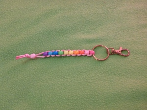Image Description: a short beaded-lanyard make of pink rat-tail cord with a bronze-coloured key-ring/split ring and lobster-claw clasp at the end. The beads are a rainbow spectrum of acrylic beads with a pale-pink heart-shaped bead as a stopper. The colour spectrum is hot-pink, pale-pink, red, orange, yellow, green, dark-blue, light-blue, purple