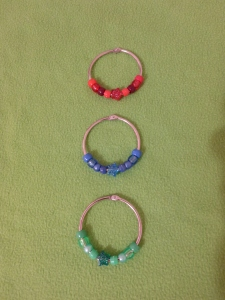 Image Description: A verticle picture of three 50 cm ring-binders from Daiso with beads. The first ring has red-themed beads, the second ring has blue-themed beads and the third ring has green-themed beads. The bead pattern is acrylic, transparent, pearl, hour-glass, glittery star-bead, hour-glass, pearl, transparent, acrylic.