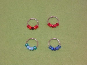 Image Description: there are four silver 30 binder-rings from Daiso in the picture. The top two are red themed bead-rings, from left to right, the first top ring has the following beads:  transparent red, acrylic red, pearlized cranberry-red, acrylic red, transparent red. The second top ring has the following beads: transparent red, acrylic red, glittery-red, acrylic red, transparent red. The bottom two are blue themed bead-rings, from left to right, the first bottom ring has the following beads: transparent light-blue, acrylic light-blue, pearlized light-blue, acrylic light-blue, transparent light-blue. The second bottom ring has the following beads: the first bottom ring has the following beads: transparent dark-blue, acrylic dark-blue, pearlized dark-blue, acrylic dark-blue, transparent dark-blue