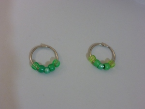 Image Description: two silver 30 cm binder-rings from Daiso with green beads on them. From left to right, the first ring has the following beads: transparent green, acrylic green, pearlized green, acrylic green, transparent green. The second ring has the following beads: transparent light-green, acrylic light-green, pearlized green, acrylic light-green and transparent light-green.