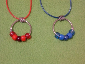 Image Description: two bead-ring necklaces on a red Rainbow String and a dark-blue Rainbow String with four chrome loops in between the Rainbow String and the key-ring/split ring. From left to right, a red themed bead-ring necklace (transparent red, acrylic red, pearlized cranberry-red, acrylic red, transparent red) and a blue themed bead-ring necklace (transparent dark-blue, acrylic dark-blue, pearlized dark-blue, acrylic dark-blue, transparent dark-blue)