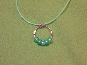 Image Description: one bead-ring necklace on a green Rainbow String with four chrome loops in between the Rainbow String and the key-ring/split ring. The bead-ring necklace has the following beads: transparent green, acrylic green, pearlized green, acrylic green, transparent green