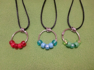 Image Description: three bead-ring necklaces on black rat-tail cord with four chrome loops in between the rat-tail cord and the key-ring/split ring. From left to right, a red themed bead-ring necklace (transparent red, acrylic red, glittery-red, acrylic red, transparent red), a blue themed bead-ring necklace (light-blue, acrylic light-blue, pearlized light-blue, acrylic light-blue, transparent light-blue) and a green themed bead-ring necklace (transparent light-green, acrylic light-green, pearlized green, acrylic light-green and transparent light-green).