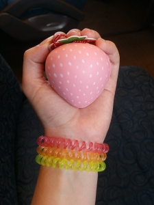 Image Description: A pale white hand holding a pale-pink squishable strawberry. Around the wrist are three telephone-cord hair-ties, a pink one, an orange one and a yellow one.