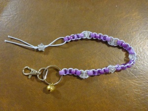 Image Description: from right to left, a chrome key-ring and lobster-claw clasp, attached to the key-ring is small gold-coloured bell. Also attached to the key ring is a long beaded lanyard made of lavender coloured elastic with with four different types of beads (acrylic, transparent, pearl, hourglass) displayed in variations of purple with a transparent-glittery-star-bead with silver glitter in between each group of beads, with a transparent-glittery-star-bead with silver glitter as a stopper at the end.