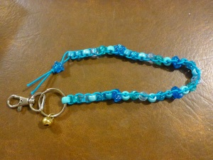 Image Description: from right to left, a chrome key-ring and lobster-claw clasp, attached to the key-ring is small gold-coloured bell. Also attached to the key ring is a long beaded lanyard made of robin's egg blue coloured elastic with with five different types of beads (acrylic, transparent, pearl, glittery, hourglass) displayed in variations of light blue with a blue-glittery-star-bead with silver glitter in between each group of beads, with a blue-glittery-star-bead with silver glitter as a stopper at the end.