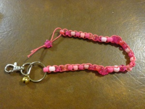 Image Description: from right to left, a chrome key-ring and lobster-claw clasp, attached to the key-ring is small gold-coloured bell. Also attached to the key ring is a long beaded lanyard made of pink coloured elastic with with five different types of beads (acrylic, transparent, hourglass, glittery, pearl) displayed in variations of light pink and dark pink with a pink-glittery-star-bead with silver glitter in between each group of beads, with a pink-glittery-star-bead with silver glitter as a stopper at the end.