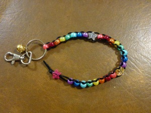 Image Description: from right to left, a chrome key-ring and lobster-claw clasp, attached to the key-ring is small gold-coloured bell. Also attached to the key ring is a long beaded lanyard made of black rat-tail cord with eight pearl beads (pink, red, orange, yellow, green, light blue, dark blue and purple), a transparent-glittery-star-bead with silver glitter, another group of eight pearl beads (pink, red, orange, yellow, green, light blue, dark blue and purple), a transparent-glittery-star-bead with gold glitter, another group of eight pearl beads (pink, red, orange, yellow, green, light blue, dark blue and purple), with a pink-glittery-star-bead with silver glitter as a stopper at the end.