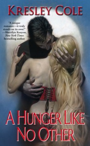 Image Description: The book-cover of A Hunger Like No Other by Kresley Cole (text is in red). In the background of the cover is an image of the moon against a blue background, in the foreground is a couple embracing. The male (dark clothes and black hair) is embracing a blonde woman (who is positioned with her back facing towards the audience so her long blonde hair can cascade down her back).