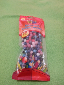 Image Description: a 50 gram packet of assorted coloured acrylic beads with the title,