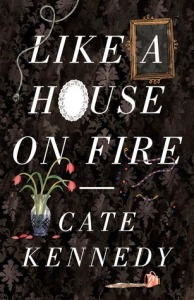 Image Description: book cover of Like A House On Fire by Cate Kennedy. The cover has a black fleur-de-lis wallpaper-like background, with the title of the book in white text taking up most of the foreground. There's a gray electrical cord snaking across the L in Like, there's a gilded picture frame around the letter A, there is a white oval-shaped serving platter in place of an O in the word House, there's a vase of wilting red tulips and a split cup of tea or coffee down the bottom of the cover.