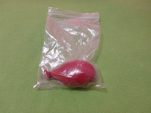 Image Description: a large red balloon sealed inside a transparent-plastic zip-lock bag.