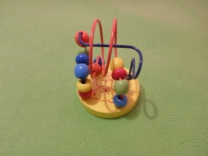 Image Description: a two-wired bead maze set into a round wooden base. The base is painted yellow with an outline of a teddy-bear in orange paint. The two wires are blue and orange; the blue wire goes straight across while the orange wire twirls in two circles. Both wires are strung with red, yellow, blue, orange and green wooden beads.