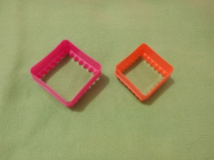 Image Description: from left to right, two square crimped biscuit cutters, the first one is larger and pink and the second one is smaller and orange.