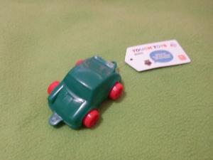Image Description: a small green plastic car with red plastic wheels and a white tag attached to the car with text displayed Tough Toys - Mini.