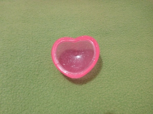 Image Description: a heart-shaped glitter-studded clear plastic popper made of thick pink plastic.