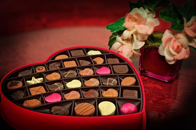 Image Description: a red circular table with a red heart-shaped-box of chocolates next to a small red square glass-vase with pink and white roses inside the vase.