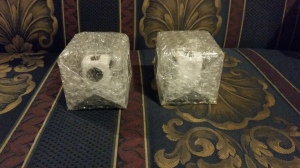 Image Description: two square objects covered in bubble-wrap sitting on my navy-blue and gold fleur-de-lis print couch, you can see inside the bubble-wrap a little to see a white and black fidget-cube inside each box.
