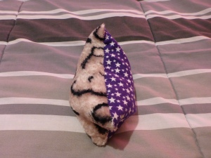 Image Description: a small bean bag made from grey, white and black tiger-print fur on one side and white-stars-on-purple flannelette on the other. It sits on top of light-grey and dark-grey striped blanket.