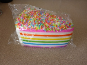 a triangular slice of white layer-cake with rainbow-coloured layers (pink, orange yellow, light blue, purple) with a layer of multi-coloured sprinkles on top of the cake.