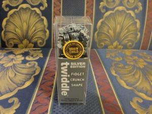Image Description: a silver Twiddle puzzle inside a transparently clear box.