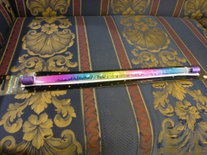 Image Description: a Rainbow Glitter Baton. A long plastic tube with rainbow coloured segments along it with silver glitter inside it.
