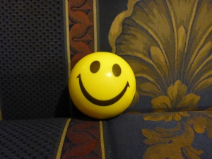 Image Description: smiley face stress-ball. A stress-ball that resembles a yellow smiley face.