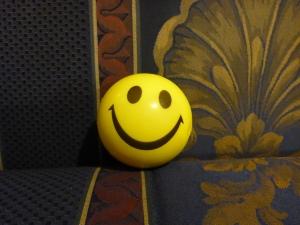 Image Description: smiley face stress-ball. A stress-ball that resembles a yellow smiley face.