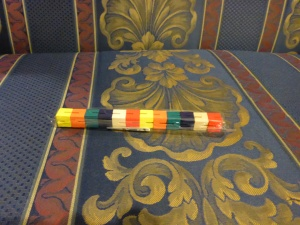 Image Description: wooden puzzle stick. It's a puzzle currently in the shape of vertical line, with seperately coloured components are are all connected, the components are coloured individually as yellow-orange-teal green-navy blue-white-red-yellow-orange-teal green-navy blue-white-red.