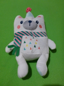 Image Description: a picture of Carrie. Carrie is a polar-bear weighted-plushie with a light-blue and pink party hat, pink blush-circles on both cheeks, wearing a stripped pink and green scarf with mulit-coloured triangles on her stomach. Carrie sits on top of a lime-green blanket.