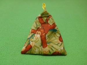 Image Description: a triangle-shaped bean-bag with a yellow tag at the end. The fabric is an olive green colour with brown monkeys printed on them.