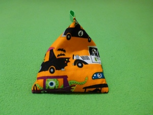 Image Description: a triangle-shaped bean-bag with a green tag at the end. The fabric is orange with prints of Halloween creatures in numbered race cars. Think along the lines of Hanna Barbera Wacky Races meets The Nightmare Before Christmas.