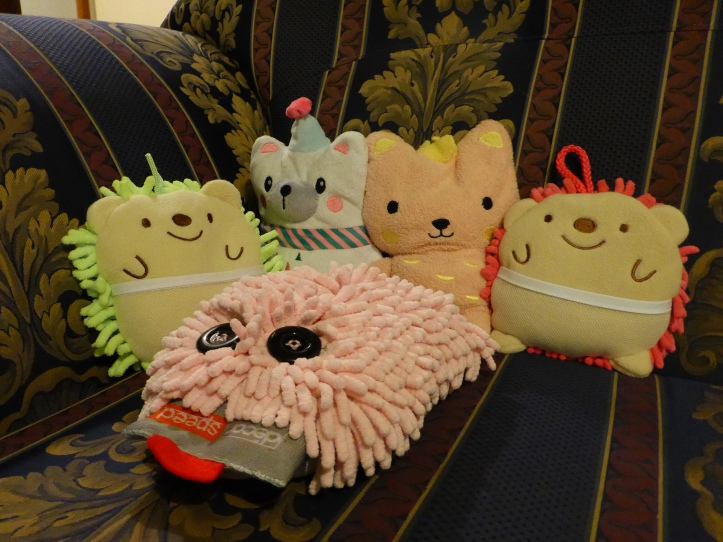 Image Description: a collection of weighted plushies sitting in an upright position on my navy-blue and golden fleur-de-lis patterned couch. From left to right, Daisy (yellow hedgehog sponge from Daiso), Carrie (a questionable Christmas-themed polar-bear), Contessa (pink-cat plushie with a yellow crown), Poppy (pink hedgehog sponge From Daiso) and in the center is Flossy (a light-pink chenille-duster with two black buttons and a red tongue attached)