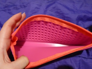 Image Description: a pale-white hand holding  one end of a bright-pink pencil-case open so that the viewer can see the inside of the pink pencil-case, it has the eight rows of indented bubbles across one side of the pencil-case.