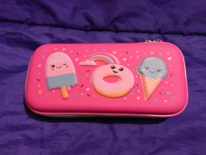 Image Description: Hoopla Sweet Collection Stationery Pencil-case. The pencil-case is pink and has clip-art pictures of an ice-cream-on-a-stick with a smiley face, a doughnut-with-pink-icing also with a smiley face and an ice-cream-cone with blue-gelato and a smiley face. There are also a single cloud and a rainbow.