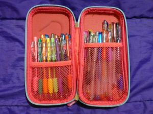Image Description: The insides of the Hoopla Sweets Collection pencil-case. It's pink with a couple of sections of netting to separate the two halves of the pencil-case. Within the netting sections are a rainbow collection of pens, glitter pens, and metallic gel pens.