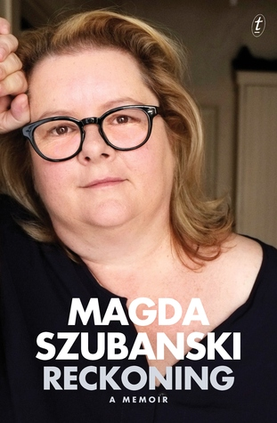 Image Description: the book cover of Reckoning: A Memoir by Magda Szubanski. It's a head and torso photo of Magda Szubanski, whom is also wearing round black glasses, a black long sleeved shirt and leaning against a doorframe.