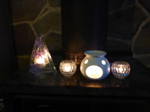 Image Description: from left to right, a triangle shaped tea-light candle holder with purple flowers painted on the front, a small glass tea-light candle holder, a white oil burner from Dusk with a tea-light candle inside and another small glass tea-light candle holder.