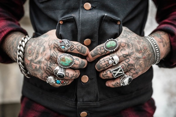 Image Description: a photo of a headless-torso with arms, presumably a person, wearing a red and black checkered long-sleeve shirt, with charcoal-grey vest and brass coloured buttons. The primary focus of the photo is of the hands, the heavily tattooed hands and fingers are displayed with unique style ring on every finger and the thumbs of each hand hooked into the pockets on either side of the vest. Around both wrists are chrome-coloured bracelets, the left wrist has a thick-chain-link style bracelet, and the right wrist has a thick chrome-coloured band with a black intricate pattern engraved into the band.