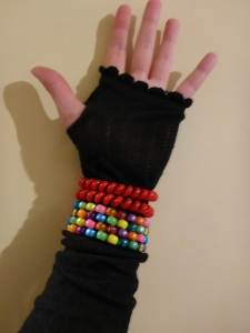 Image Description: a pale skinned hand wearing a black finger-less glove. Around the wrist section of the glove are two red opaque telephone-cord hair-ties and pony-bead bracelet comprising four rows of multi-coloured pony-beads.