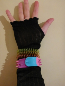 Image Description: a pale skinned hand wearing a black finger-less glove. Around the wrist section of the glove are three transparent telephone-cord hair-ties, the first one is transparent yellow, transparent orange, and transparent pink. Below the transparent telephone-cord hair-ties, is a blue-pink-purple Smiggle snap-bracelet with rubber spikes.