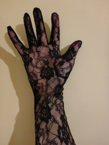 Image Description: a pale hand encased in a glove made out of black lace with small black flowers (made out of black-lace) scattered along the glove.
