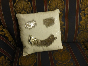 Image Description: a large square cushion from KMart with Mermaid Sequins, the sequins display one side white and the other side silver when you brush them in a different direction. The current picture displays a smiley face with silver patches of silver sequins with the white sequins acting as a contrast.
