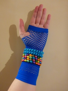 Image Description: Image Description: a pale skinned hand wearing a blue fish-net style glove. Around the wrist section of the glove are two light-blue opaque telephone-cord hair-ties and pony-bead bracelet comprising four rows of multi-coloured pony-beads.