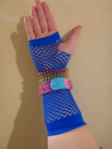 Image Description: a pale skinned hand wearing a blue fish-net style glove. Around the wrist section of the glove are three transparent telephone-cord hair-ties, the first one is transparent yellow, transparent orange, and transparent pink. Below the transparent telephone-cord hair-ties, is a blue-pink-purple Smiggle snap-bracelet with rubber spikes.