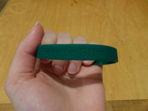 Image Description: A wooden surface is in the background, in the foreground is a pale-white hand holding a thick dark-green rubber wrist band with