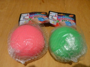 "Image Description: from left to right, a pink ball in a clear plastic bag inside a white mesh bag with the cardboard label reading ""hi-bounce stretch ball"" in blue, pink and green writing, next to the pink ball is a green ball in a clear plastic bag inside a white mesh bag with the cardboard label reading ""hi-bounce stretch ball"" in blue, pink and green writing. Both of them are resting on top of a wooden surface."