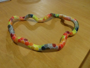 Image Description: a picture of a Tangle JR uncoiled so it forms a circle on a flat wooden surface, there is a spectrum of rainbow-coloured hexagons visible.