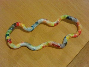 Image Description: a picture of a Tangle JR uncoiled so it forms a circle on a flat wooden surface (the reverse side of the previous picture), there is a spectrum of rainbow-coloured hexagons visible, but the colours appear to be muted or faded.